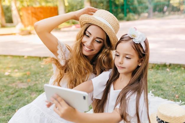 Красивая девушка в белом платье держит смартфон и делает селфи со смеющейся мамой, идущей по улице. внешний портрет радостной молодой женщины в шляпе представляя пока дочь брюнет принимая фото. Бесплатные Фотографии