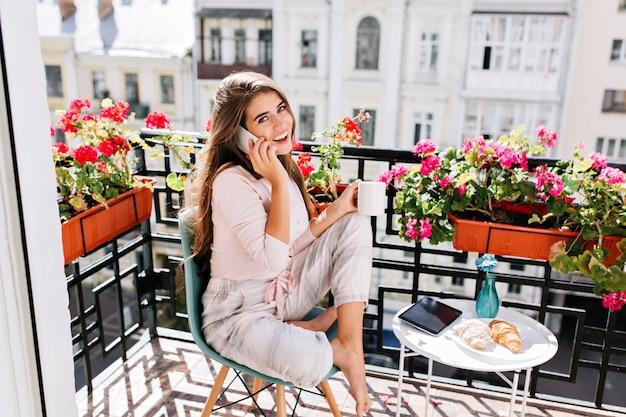 Bella ragazza in pigiama facendo colazione sul balcone nella mattina soleggiata. ha conseguito una tazza, parlando al telefono sorridendo. Foto Gratuite