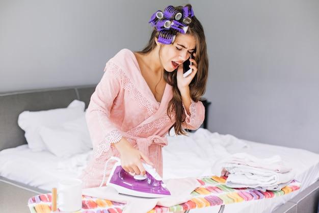Bella ragazza in accappatoio rosa e bigodino stirare i vestiti e parlare al telefono a casa. sembra stupita e impegnata. Foto Gratuite