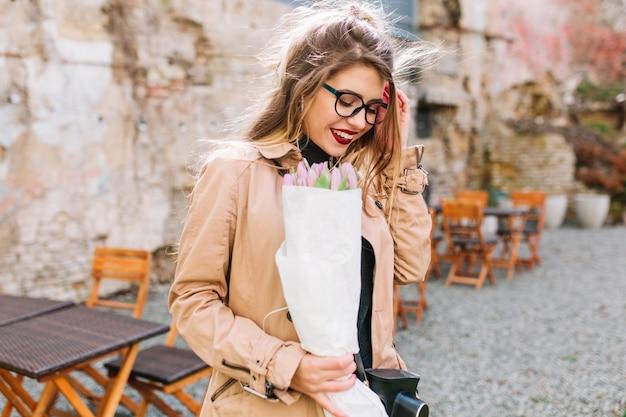 예쁜 소녀는 예상치 못한 선물을 받고 종이 봉지에 꽃을 들고 혼란스럽게 웃었습니다. 야외 카페에서 포즈를 취하는 튤립 부케와 안경과 베이지 색 재킷에 당황한 젊은 여자. 무료 사진