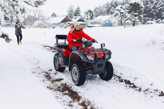 A pretty girl riding a quadrocycle in a picturesque snowy area Premium Photo