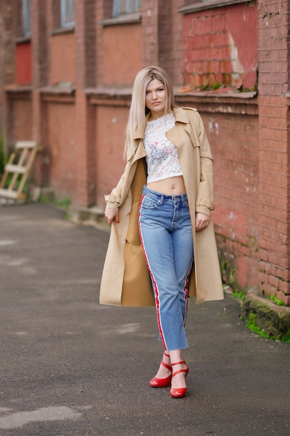 Pretty girl in short jeans and raincoat walking on the street after the rain Premium Photo