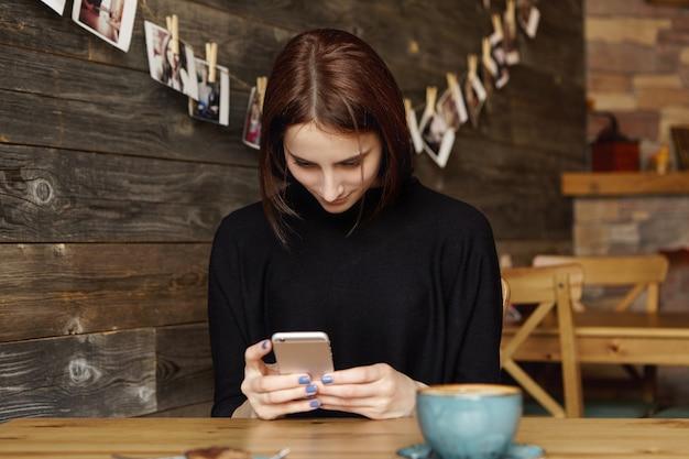 携帯電話で無線インターネット接続を使用して、マグカップでカフェのテーブルに座っているきれいな女の子 無料写真