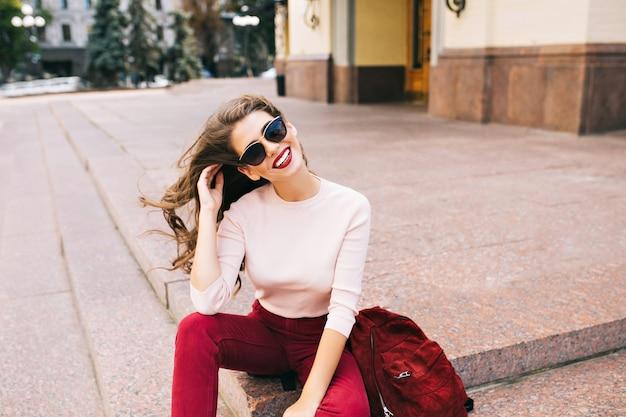 Bella ragazza in occhiali da sole in pantaloni vinosi è seduta sulle scale in città. i suoi lunghi capelli sono sospinti dal vento, sorride. Foto Gratuite