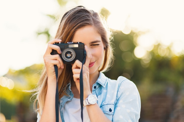 Pretty girl taking photos with a vintage camera on a sunny day Free Photo