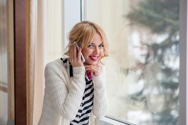 Pretty girl talking on the phone near a window, blonde Premium Photo
