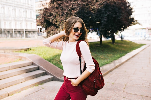 Pretty girl in vinous pants in sunglasses is walking on the street with a bag. she is smiling and looks enjoyed. Free Photo