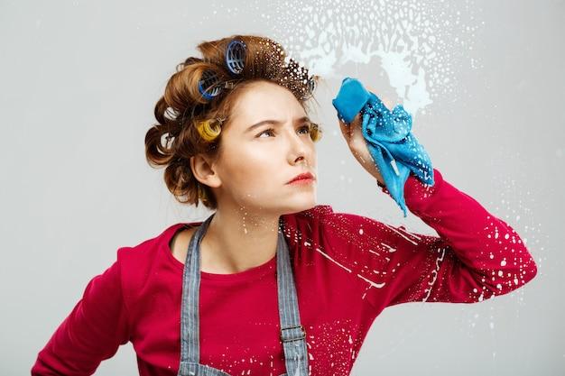 Красивая девушка смахивает окна с голубым полотенцем Бесплатные Фотографии