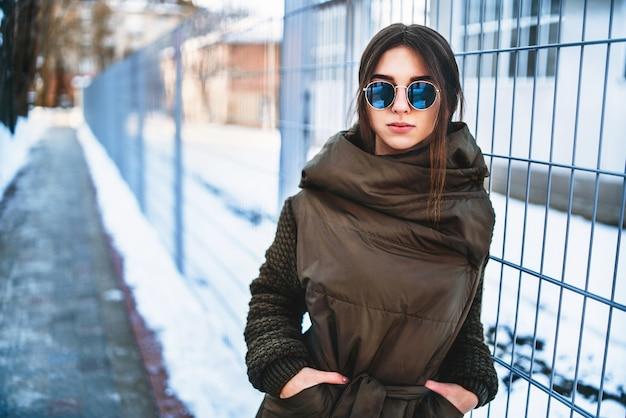 Милая девушка гуляя напольная на улице, зимнее время. Premium Фотографии