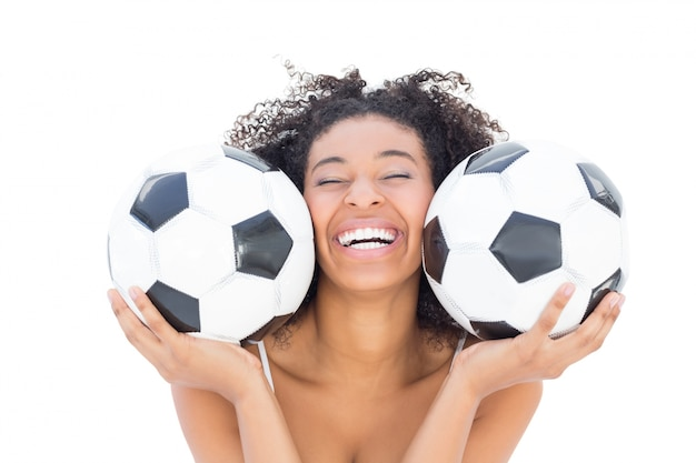 Pretty girl with afro hairstyle smiling at camera holding footballs Premium Photo