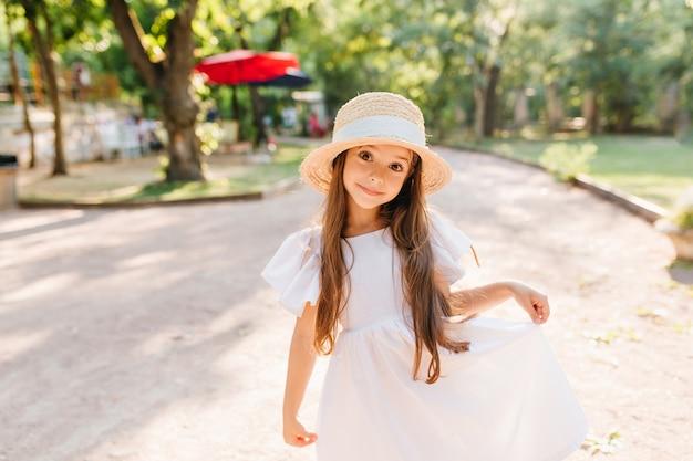夏休みの公園で楽しみながらポーズをとって美しい大きな黒い瞳を持つかわいい女の子。驚いた笑顔で道路に立っている麦わら帽子の面白い長髪の子供の屋外の肖像画。 無料写真