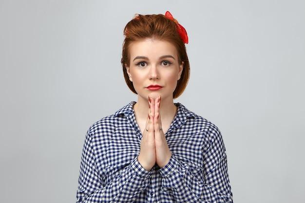 Bella ragazza con i capelli allo zenzero e rossetto rosso premendo insieme i palmi in preghiera. bella giovane donna alla moda che prega in studio, fissando la telecamera con grandi occhi pieni di speranza e forte convinzione Foto Gratuite