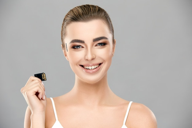 Pretty girl with her hair tightened and perfect smile holding memory card , female and technology Premium Photo