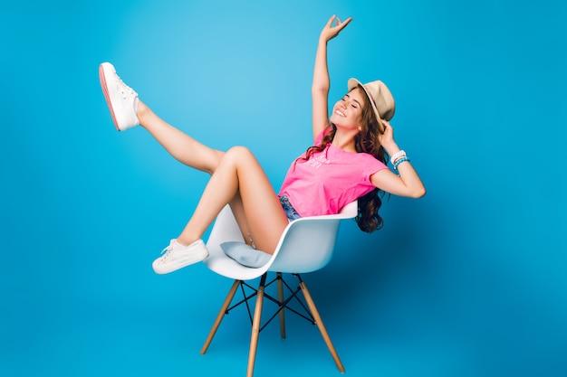 모자에 긴 곱슬 머리를 가진 예쁜 여자는 스튜디오에서 파란색 배경에 자에 놀 아 요. 그녀는 반바지, 분홍색 티셔츠, 흰색 운동화를 착용합니다. 그녀는 다리를 위로 유지하고 흥분해 보입니다. 무료 사진