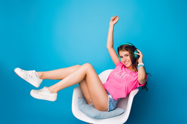 Pretty girl with long curly hair  listening to music in chair on blue background in studio. she wears shorts, pink t-shirt, white sneakers. she holds legs above and smiles to camera. Free Photo