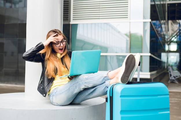 黒いガラスの長い髪のかわいい女の子は空港の外に座っています。彼女はジーンズ、黒のジャケット、黄色の靴を履いています。彼女はスーツケースに足を置き、ラップトップで話しました。彼女は驚いたようだ。 無料写真
