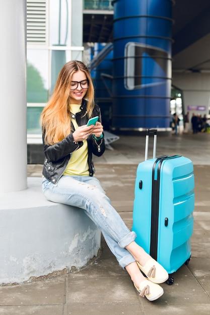 メガネの長い髪のかわいい女の子は空港の外に座っています。彼女は黄色いセーター、黒いジャケットとジーンズを着ています。彼女は近くにスーツケースを持っていて、電話でタイプしています。 無料写真