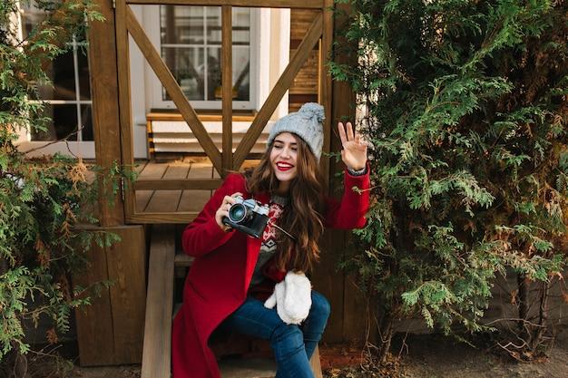 赤いコートと木製の階段の上に座ってニット帽子の長い髪のかわいい女の子。彼女はカメラを構えて横を向きます。 無料写真