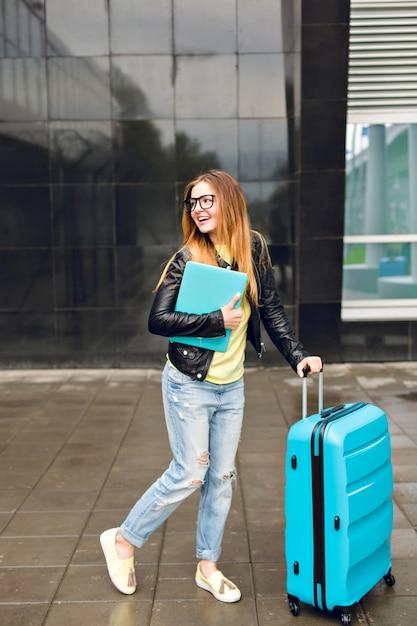長い髪のかわいい女の子が空港の外のスーツケースで歩いています。彼女はジーンズと黒のジャケットを着ており、ラップトップを持っています。彼女は幸せそうです。 無料写真