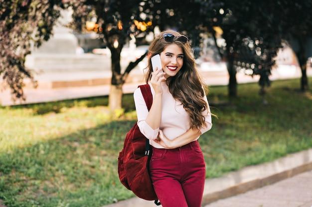 Bella ragazza con capelli lunghi in pantaloni vinosi con borsa sorride nel parco cittadino. sta parlando al telefono e sembra goduta. Foto Gratuite