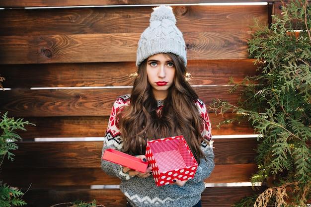 Красивая девушка с длинными волосами с пустой рождественской коробкой на деревянном. в теплой зимней одежде, выглядит недовольной. Бесплатные Фотографии