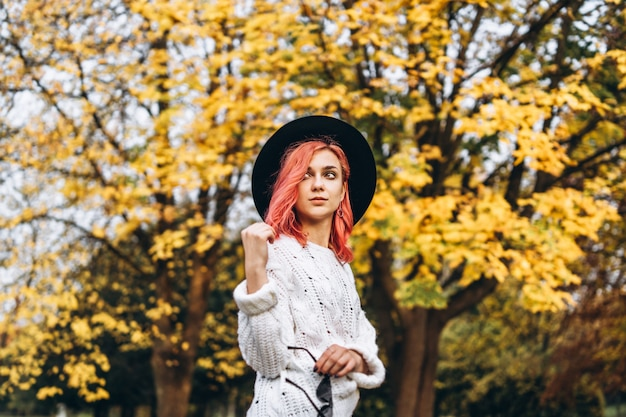 Pretty girl with red hair and hat relaxing in the park, autumn time. Premium Photo