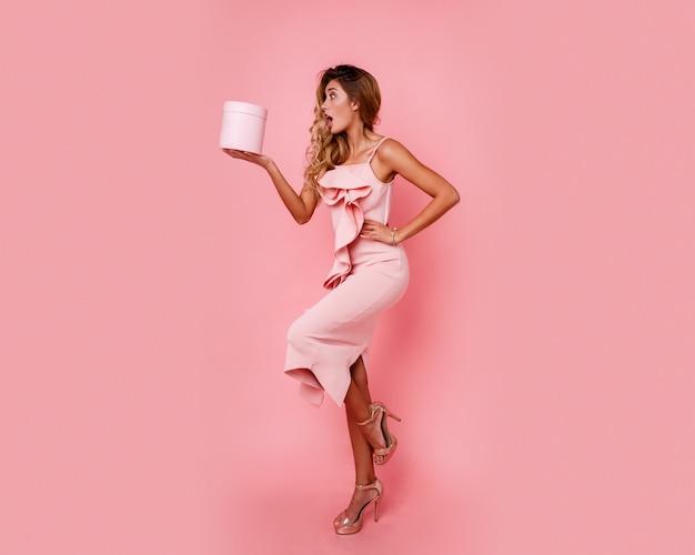 Ragazza graziosa con il fronte di sorpresa che tiene il contenitore di regalo e che controlla parete rosa in vestito rosa elegante. emozioni estatiche. Foto Gratuite