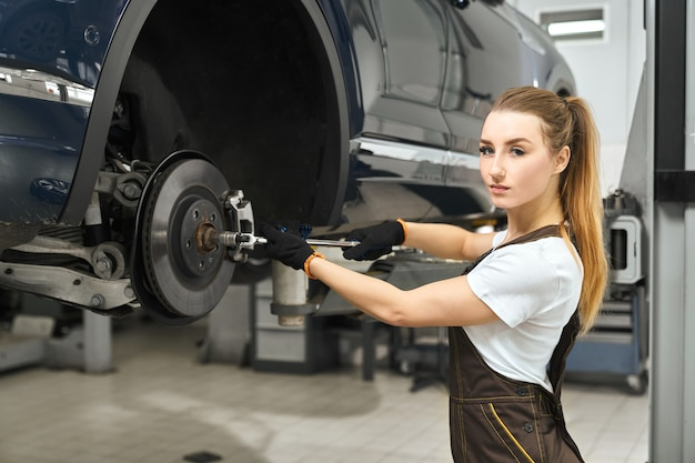 Pretty girl working as mechanic in autoservice, fixing car. Free Photo