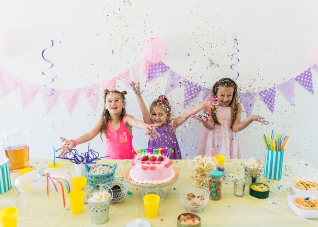 Pretty girls enjoying birthday party at home with variety of food and juice on table Free Photo