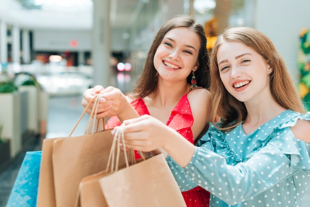 Pretty girls posing with shopping bags Free Photo