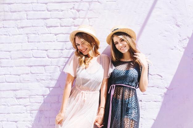 Belle ragazze in abiti estivi alla moda in posa insieme dopo una passeggiata in città e sorridente Foto Gratuite