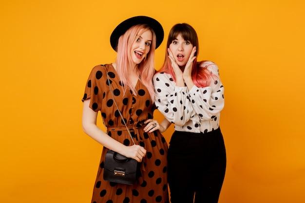 Красивые девушки с эмоциональным лицом позирует над желтой стеной Бесплатные Фотографии