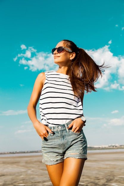 Pretty happy girl in a striped t-shirt and jeans shorts posing with glasses in the beach Free Photo