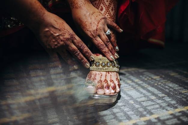 Pretty hindu bride puts on her wedding shoes Free Photo