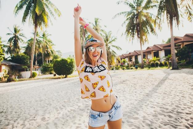 Симпатичная хипстерская женщина, идущая на пляже, танцует, слушая музыку в наушниках, в стильной красочной одежде на солнечных летних тропических каникулах в солнцезащитных очках с аксессуарами и улыбается Бесплатные Фотографии