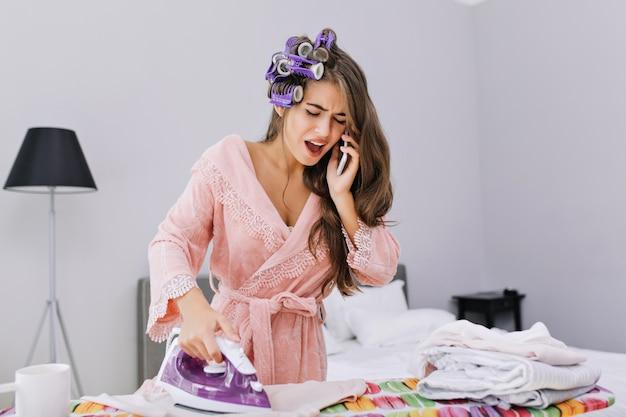 Bella casalinga in accappatoio rosa e bigodino stirare i vestiti e parlare al telefono. sembra stupita e impegnata. Foto Gratuite
