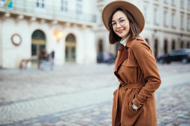 Довольно в современном коричневом пальто позирует на улице в центре города Бесплатные Фотографии