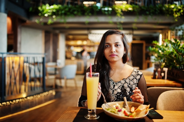 Pretty indian girl in black saree dress posed at restaurant, sitting at table with juice and salad. Premium Photo