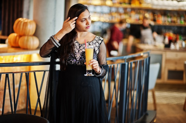 Pretty indian girl in black saree dress posed at restaurant with orange juice at hand. Premium Photo