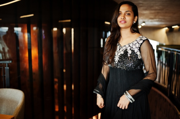 Pretty indian girl in black saree dress posed at restaurant. Premium Photo