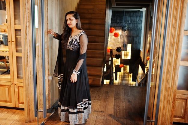 Pretty indian girl in black saree dress posed at restaurant. Premium Photo