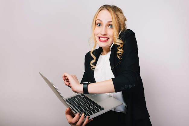 Pretty joyful blonde businesswoman with laptop talking on phone isolated. wearing office suit, stylish, fashionable, being busy, smiling, true emotions Free Photo