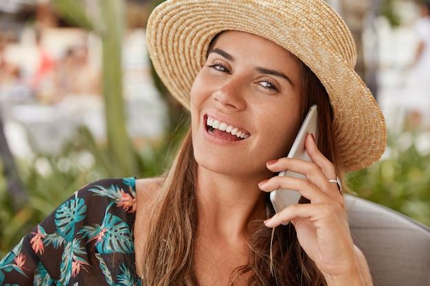 Довольно жизнерадостная самка в соломенной шляпе, восседающая на летних каникулах в тропической курортной стране, разговаривает по смартфону с родственниками, пользуется бесплатным роумингом, имеет широкую сияющую улыбку. концепция образа жизни Бесплатные Фотографии