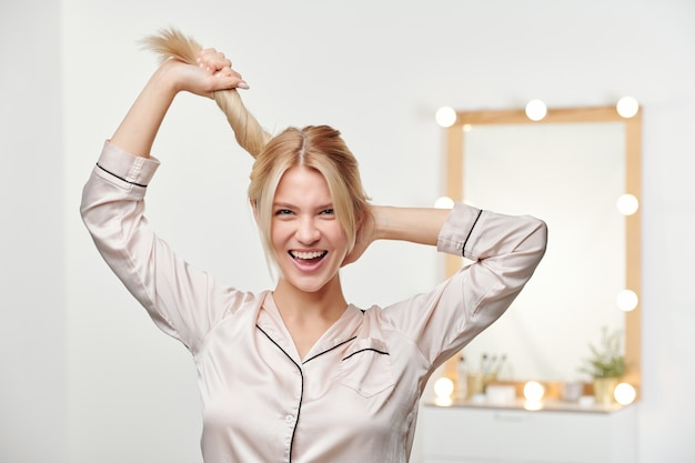 Pretty joyful girl in silk pajamas holding ponytail of her long thick blond healthy hair while standing Premium Photo