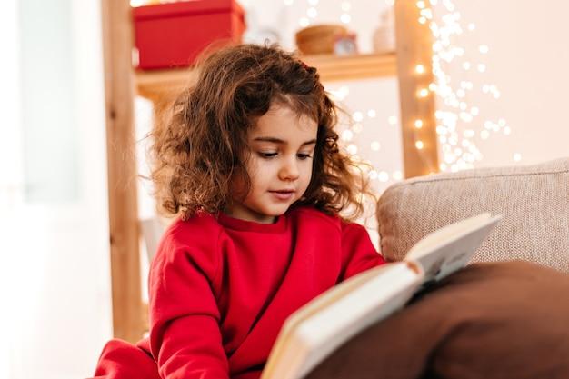 Довольно ребенок читает книгу дома. крытый выстрел фигурной маленькой девочки в красной рубашке. Бесплатные Фотографии