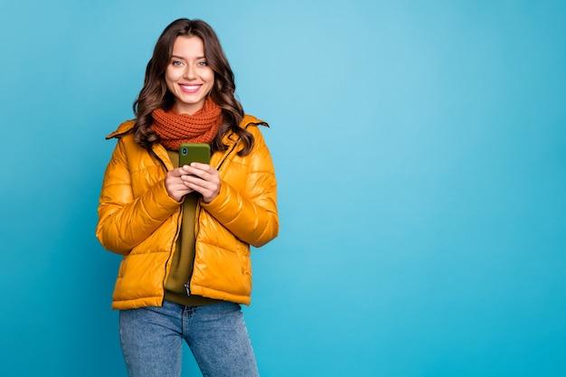 예쁜 아가씨 전화 이빨 미소 착용 가을 윈드 브레이커를 들고 프리미엄 사진