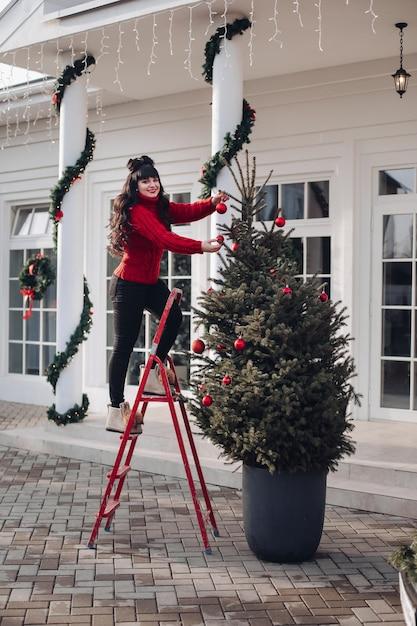 庭のクリスマスツリーを飾っている間、階段のはしごの上に立っている赤いセーターのきれいな女性 無料写真