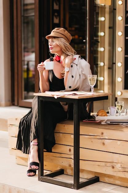 Bella signora in abito lungo e sandali neri godendo il pranzo in un caffè all'aperto e guardando lontano. affascinante ragazza bionda con cappello in attesa di un amico per mangiare insieme i croissant. Foto Gratuite