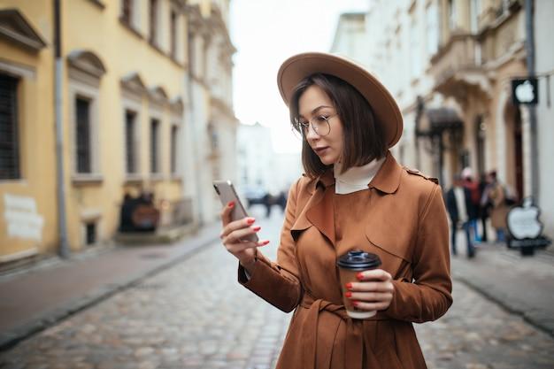 Довольно леди разговаривает по мобильному телефону, прогулки на свежем воздухе в холодный осенний день Бесплатные Фотографии