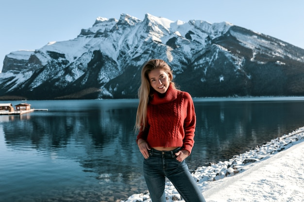 Pretty lady with white smile standing on the beach near the lake. mountains  covered with snow. wearing red knitted sweater and blue jeans. blonde long hairstyle, no makeup. Free Photo